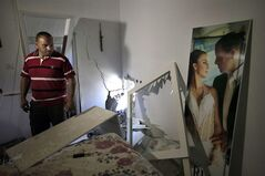 Avihai Giorno stands in his bedroom by a wedding photo of him and is wife Tammy after a rocket fired by Palestinian militants in Gaza, landed in the southern town of Sderot Thursday, July 3, 2014. Israeli military carried out airstrikes on the Gaza Strip after Palestinian militants fired rockets into Israel early Thursday. The Israeli military said the air force struck 15
