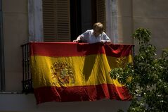 A woman hangs a Spanish flag on her balcony in front of the Royal Palace in Madrid, Spain, Wednesday, June 18, 2014, a day before 46-year-old Prince Felipe will be proclaimed king on June 19. King Juan Carlos said he was stepping aside so that fresh royal blood could rally the nation. Juan Carlos became king in 1975, two days after the death of longtime dictator Gen. Francisco Franco. (AP Photo/Emilio Morenatti)