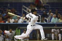 Miami Marlins' Jake Marisnick hits a single off Chicago Cubs pitcher Jason Hammel during the first inning of a baseball game in Miami, Monday, June 16, 2014. (AP Photo/J Pat Carter)