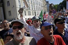 People shout slogans outside the Portuguese parliament during a protest by Portugal's main union CGTP, General Confederation of the Portuguese Workers, against cuts in salaries and pensions and others austerity measures taken by the government, in Lisbon, Thursday, July 10, 2014. (AP Photo/Francisco Seco)