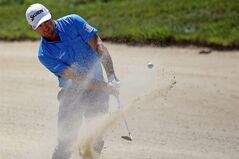 Graeme McDowell of Northern Ireland chips out of the bunker on the 5th hole, during the first day of the French Open Golf tournament at Paris National course in Guyancourt, west of Paris, France, Thursday, July 3, 2014. (AP Photo/Francois Mori)