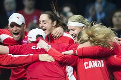 Canada's Eugenie Bouchard, second right, celebrates with teammates after defeating Vesna Dolonc from Serbia during a Federation Cup tennis match in Montreal, Sunday, February 9, 2014. THE CANADIAN PRESS/Graham Hughes