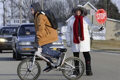 Bundled against the below-zero wind chill, educational assistant Pam Whitted helps students cross the street safely in front of Eastbrook South Elementary School in Upland, Ind., on Tuesday, Jan. 22, 2013. All Grant County schools were on a two-hour delay because of the cold weather. (AP Photo/Chronicle-Tribune, Jeff Morehead)