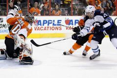 Philadelphia Flyers goalie Ilya Bryzgalov, left, deflects a shot by Winnipeg Jets' Blake Wheeler, right, in the first period of an NHL hockey game Saturday, in Philadelphia.
