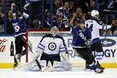Tampa Bay Lightning's Cory Conacher (L) and Benoit Pouliot celebrate a goal as Winnipeg Jets goalie Ondrej Pavelec and defenceman Grant Clitsome react during the first period in Tampa.