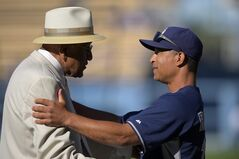 Hall of famer Don Newcombe, left, talks with San Diego Padres bench coach Dave Roberts prior to a baseball game between the Los Angeles Dodgers and the Padres, Saturday, July 12, 2014, in Los Angeles. (AP Photo/Mark J. Terrill)