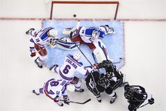 New York Rangers goalie Henrik Lundqvist, of Sweden, above, sits on the ice after the puck, shot by Los Angeles Kings right wing Justin Williams, below left, enters the goal during the first period in Game 5 of the NHL hockey Stanley Cup finals, Friday, June 13, 2014, in {city. (AP Photo/Mark J. Terrill)
