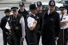 British police officers gather outside Portcullis House after the arrival of Pfizer CEO Ian Read for a committee hearing in London, Tuesday, May 13, 2014. British lawmakers are expected to pressure the chief executive of Pfizer to guarantee jobs should the American company succeed in taking over London-based AstraZeneca, when they question him on Tuesday. Ian Read faces Parliament's Business Innovation and Skills Committee to defend his company's $106 billion cash and stock offer. The U.S. drugmaker has sought in writing to ease worries that British jobs will be lost — but has so far failed to convince skeptical lawmakers. (AP Photo/Matt Dunham)