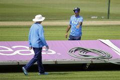 India's captain and wicketkeeper Mahendra Singh Dhoni, right, and head coach Duncan Fletcher talk before pushing the covers aside to check the wicket during a training session the day before the start of the third cricket test match of the series between England and India at The Ageas Bowl in Southampton, England, Saturday, July 26, 2014. (AP Photo/Matt Dunham)