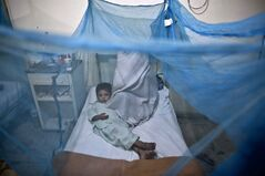 "FILE - In this file photo taken Monday, Nov. 11, 2013, a Pakistani child suffering from the mosquito-borne disease, dengue fever, lies in a bed, next to his mother, covered with a net at an isolation ward of a hospital in Rawalpindi, Pakistan. The most advanced vaccine for dengue only offers modest protection but could still help millions of people avoid the devastating effects of the disease known as ""breakbone fever,"" according to a large trial. There is no treatment or vaccine for dengue, which causes symptoms including fever, severe joint pain, headaches and bleeding. About half the world's population is at risk from the mosquito-borne disease, which sickens about 100 million people every year, mostly in Asia, Africa and Latin America. (AP Photo/Muhammed Muheisen, File)"