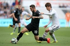 Burnley's Danny Ings battles for the ball with Swansea City's Ki Sung-Yueng during the English Premier League match at the Liberty Stadium, Swansea, Wales, Saturday Aug. 23, 2014. (AP Photo/PA, Nick Potts) UNITED KINGDOM OUT NO SALES NO ARCHIVE