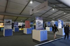 Visitors walk by an empty stand set up to showcase the F-35 Lighting II joint strike fighter during Farnborough International Air Show, Farnborough, England, Wednesday, July 16, 2014. The Pentagon is resuming test flights of its new-generation F-35 fighter while investigating the cause of an engine fire last month, but the plane will operate with restrictions and will not fly in the Farnborough International Airshow in England. (AP Photo/Sang Tan)