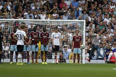 A supporter runs onto the pitch and kicks the ball set up for a Tottenham Hotspur's free kick against West Ham United during their English Premier League soccer match at Upton Park, London, Saturday, Aug. 16, 2014. (AP Photo/Sang Tan)
