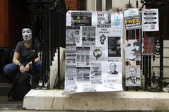 A supporter of WikiLeaks founder Julian Assange holds a vigil outside the Ecuadorian Embassy in London to mark his two years of refuge at the embassy, Thursday, June 19, 2014. Julian Assange entered the embassy in June 2012 to gain political asylum to prevent him from being extradited to Sweden, where he faces allegations of sex crimes, which he denies. (AP Photo/Sang Tan)
