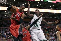 Toronto Raptors guard Terrence Ross (31) hauls down a rebound against Boston Celtics forward Brandon Bass (30) during the first quarter of an NBA basketball game in Boston, Wednesday, Jan. 15, 2014. (AP Photo/Charles Krupa)