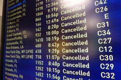 A board displays cancelled flights at Logan International Airport in Boston on Saturday evening, Feb. 15, 2014. Another round of snow made its way into the Northeast on the heels of a storm that brought snow and ice to the East Coast, caused at least 25 deaths and left hundreds of thousands without power. (AP Photo/Elise Amendola)