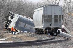 CN workers assess the scene of a train derailment south of St. Norbert Sunday. No hazardous materials were involved in the derailment.