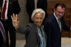 International Monetary Fund (IMF) Managing Director Christine Lagarde, center, waves to photographers accompanied by Mexico Secretary of Finance Luis Videgaray after taking part in the inauguration of an economic forum at the National Palace in Mexico City, Thursday, June 26, 2014. (AP Photo/Moises Castillo)