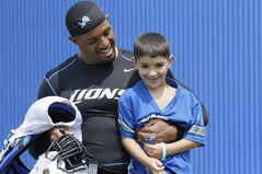 Detroit Lions inside linebacker Brandon Hepburn carries Christopher Mili, 6, before an NFL football training camp in Allen Park, Mich., Thursday, July 31, 2014. (AP Photo/Carlos Osorio)