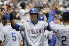 Texas Rangers' Alex Rios high fives teammates after scoring from second on a Chris Gimenez single to right field during the second inning of a baseball game against the Detroit Tigers in Detroit, Thursday, May 22, 2014. (AP Photo/Carlos Osorio)