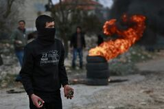 A Palestinian holds stones to hurl at Israeli forces during clashes at a protest against the expansion of the nearby Jewish settlement Ofra outside the village of Silwad, near the West Bank city of Ramallah, Friday, Jan. 10, 2014. (AP Photo/Majdi Mohammed)