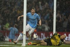 Manchester City's Edin Dzeko, left, celebrates after scoring his first goal against Aston Villa during their English Premier League soccer match at the Etihad Stadium, in Manchester, England, Wednesday May 7, 2014. (AP Photo/Jon Super)