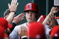 Los Angeles Angels' C.J. Cron is congratulated in the dugout after hitting a home run in the second inning of a baseball game against the Kansas City Royals at Kauffman Stadium in Kansas City, Mo., Friday, June 27, 2014. (AP Photo/Colin E. Braley)