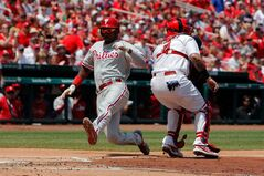 Philadelphia Phillies' Domonic Brown, left, scores on a three-run double hit by Cody Asche as St. Louis Cardinals catcher Yadier Molina, right, waits for the ball during the second inning of a baseball game on Sunday, June 22, 2014, in St. Louis. (AP Photo/Scott Kane)