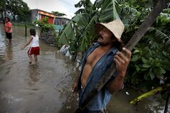 Benito Garcia Velasquez stands with his family outside of their flooded home after heavy rains caused by Tropical Storm Barry in the city of Veracruz, Mexico, Thursday June 20, 2013. Barry has weakened to a tropical depression but is still producing torrential rains. (AP Photo/Felix Marquez)