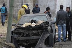 Hats belonging to victims sit on the hood of a damaged car as emergency workers gather a the scene where a truck loaded with fireworks exploded during a religious procession in the town of Nativitas, Mexico, Friday March 15, 2013. A truck loaded with fireworks exploded during a religious procession in this rural village in central Mexico, killing at least nine people and injuring dozens more, authorities said. (AP Photo/J. Guadalupe Perez)