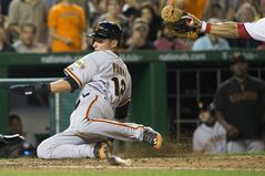 San Francisco Giants' Joe Panik, left, slides past Washington Nationals catcher Wilson Ramos to score a run on a double hit by teammate Travis Ishikawa during the eighth inning of a baseball game on Friday, Aug. 22, 2014, in Washington. The Giants defeated the Nationals 10-3. (AP Photo/Evan Vucci)