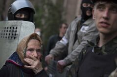 AP10ThingsToSee - A woman watches as a group of pro-Russian demonstrators storm the military prosecutor's office in Donetsk, Ukraine on Sunday, May 4, 2014. Pro-Russian forces and their supporters have been seizing and ransacking government buildings across eastern Ukraine amid a mounting anti-government insurgency in the former Soviet nation. (AP Photo/Alexander Zemlianichenko)