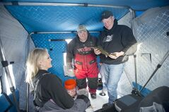 Steve Dahl, owner of the Perch Patrol, checks in with clients Lisa and Matt Johnson of Forest Lake, Minn. Matt is holding a walleye, Saturday, Feb. 8, 2014. (AP Photo/Jackie Lorentz)