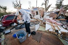Traci Krus looks at a pictures of her family that she found in her damaged home Saturday Oct. 5 2013 in Wayne, Neb. A tornado struck the northeast Nebraska town Friday, causing millions of dollars in damage, but the mayor says no one was killed and the injuries reported have been minor. Mayor Ken Chamberlain said that officials have accounted for all residents in town. (AP Photo/Dave Weaver)