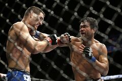 Lyoto Machida, right, hits Chris Weidman during their mixed martial arts middleweight title bout at UFC 175 Saturday, July 5, 2014, in Las Vegas. (AP Photo/John Locher)
