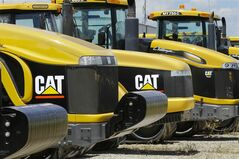 FILE - In this June 20, 2012 file photo, earth-moving tractors and equipment made by Peoria, Ill.-based Caterpillar Inc. are seen in Clinton, Ill. Caterpillar and several mining companies have evacuated employees from Liberia. British Airlines has canceled flights to the region. Exxon and Chevron say they're waiting to see whether public health authorities can contain the Ebola outbreak in three West African countries. (AP Photo/Seth Perlman, File)