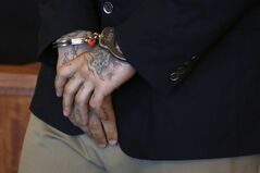 The tattooed hands of New England Patriots football player Aaron Hernandez are cuffed for a hearing in Bristol County Superior Court in Fall River, Mass., Wednesday, July 9, 2014. (AP Photo/Dominick Reuter, Pool)