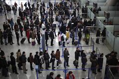 FILE - In this Jan. 20, 2012, file photo, passengers queue up for a security check at Pudong International Airport in Shanghai, China. The Transportation Security Administration is requiring passengers at some overseas airports that offer U.S.-bound flights to power on their electronic devices, the agency said Sunday, July 6, 2014. It says devices that won't power up won't be allowed on planes, and those travelers may have to undergo additional screening. (AP Photo/Eugene Hoshiko, File)