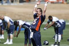 FILE - In this June 2, 2014 file photo, Denver Broncos quarterback Peyton Manning stretches during an NFL football organized team practice at the Broncos training facility in Englewood, Colo. After throwing for more yards and touchdowns than anyone in NFL history, Manning had to say good bye to wide receiver Eric Decker and running back Knowshon Moreno, who combined for 3,154 yards from scrimmage and 25 touchdowns in the lead-up to the Super Bowl. Replacing Decker are coveted free agent Emmanuel Sanders and prized rookie Cody Latimer, both of whom have spent plenty of 1-on-1 time with Manning this offseason. (AP Photo/Ed Andrieski, FIle)