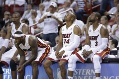 ADVANCE FOR WEEKEND EDITIONS, JULY 19-20 - FILE - In this May 23, 2013, file photo, Miami Heat players, from left, Chris Bosh, LeBron James, Ray Allen and Dwyane Wade wait for the start of overtime during Game 1 in their NBA basketball Eastern Conference finals playoff series against the Indiana Pacers in Miami. No one was calling the Heat back after James announced that he was leaving for Cleveland. Fear and panic were settling in among the Heat brass. Then Bosh called to say he was staying and over the next few days, even without James, the Heat started putting together a team they think can compete. (AP Photo/Lynne Sladky, File)