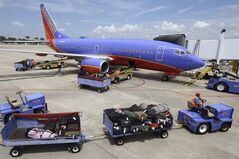 In this June 19, 2014 photo, baggage carts are towed to a Southwest Airlines jet at Bill and Hillary Clinton National Airport in Little Rock, Ark., as the Boeing 737 is serviced. Southwest Airlines reports quarterly financial results on Thursday, July 24, 2014. (AP Photo/Danny Johnston)