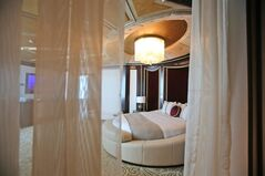 This May 19, 2014 photo shows the master bedroom in the Abu Dhabi Suite at the St. Regis in Abu Dhabi, United Arab Emirates. The nearly 24,000 square foot two-story suite, which sells for a nightly rate of $21,500, is suspended 720 feet above ground between the two buildings of the Nation Towers development. It has three bedrooms, a spa, a cinema, a bar area, two kitchens and a 360-degree panoramic view of the city, the islands, and the Sheikh Zayed Grand Mosque. The suite has 19 chandeliers made of Bohemian crystal, and an elevator that takes guests to ground level in total privacy, bypassing the rest of the hotel. (AP Photo/Kamran Jebreili)