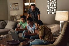 This image released by Disney shows Jon Hamm, background center, in a scene with, seated from left, Suraj Sharma, Madhur Mittal and Pitobash in a scene from