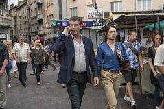 This image released by Relativity Media shows Pierce Brosnan, center, and Olga Kurylenko in a scene from the film,