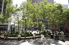 In this photo of July 15, 2011, people relax under shade trees at the British Garden at Hanover Square in New York. Out of the ashes of 9/11 has risen a vibrant neighborhood packed with new restaurants and hotels, places to live and spots to shop, along with many ways to pay respects to an area some worried would never come back. A decade after the attack on the World Trade Center, Lower Manhattan draws roughly 9 million of the city's nearly 50 million visitors a year, including the area around ground zero. (AP Photo/Mark Lennihan)
