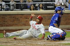 Philadelphia Phillies' Marlon Byrd, left, scores at home plate behind New York Mets catcher Travis d'Arnaud on a single by Cody Asche in the seventh inning of a baseball game at Citi Field, Friday, Aug. 29, 2014, in New York. (AP Photo/Kathy Kmonicek)