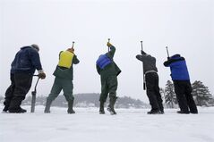 Inmates from the Moriah Shock Incarceration Correctional Facility, wearing green, work with volunteers breaking off ice blocks from Lake Flower that will be used to construct the Saranac Lake Winter Carnival ice palace on Monday, Jan. 28, 2013, in Saranac Lake, N.Y. (AP Photo/Mike Groll)