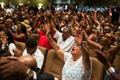 People raise their arms during the funeral service for Michael Brown at Friendly Temple Missionary Baptist Church in St. Louis, Monday, Aug. 25, 2014. Hundreds of people gathered to say goodbye to Michael Brown, the 18-year-old shot and killed Aug. 9 in a confrontation with a police officer that fueled almost two weeks of street protests. (AP Photo/New York Times, Richard Perry, Pool)