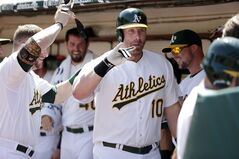 Oakland Athletics' Adam Dunn celebrates in the dugout after his two-run home run against the Seattle Mariners during the first inning of a baseball game on Monday, Sept. 1, 2014, in Oakland, Calif. (AP Photo/Marcio Jose Sanchez)