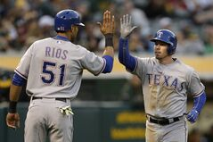 Texas Rangers' Donnie Murphy, right, is congratulated by Alex Rios, left, after Murphy hit a two-run home run off Oakland Athletics' Drew Pomeranz in the fourth inning of a baseball game Monday, June 16, 2014, in Oakland, Calif. (AP Photo/Ben Margot)